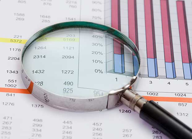 Magnifying class sitting on top of financial data