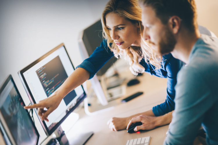 Male and female coding professional collaborating on computer