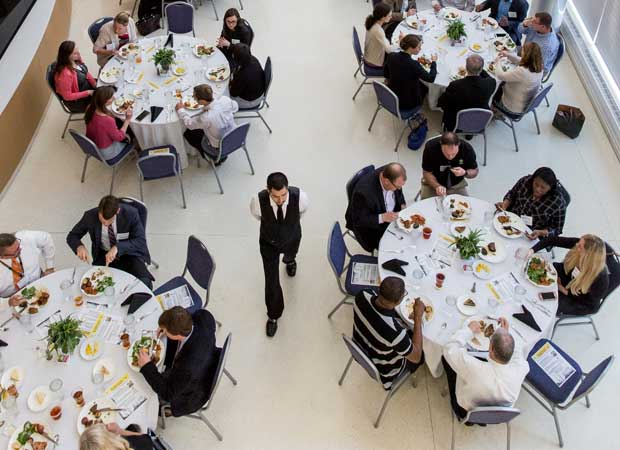 Attendees eating lunch around tables at conference