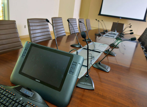 View of conference table featuring A/V monitor, screen, and microphones