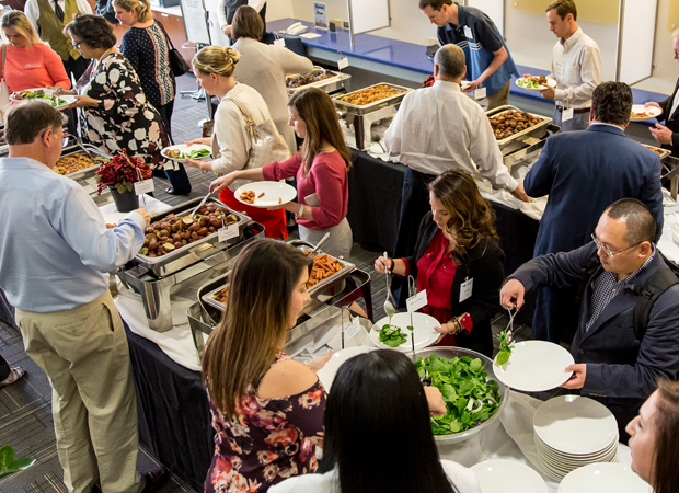Individuals serving themselves food in a buffet line
