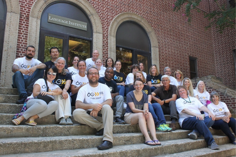Language Institute instructors sit at steps in front of building wearing 60th anniversary shirts