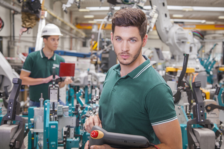 Image of mechanical workers working with one man looking straight into the camera