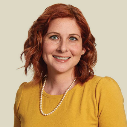 Nicole de Vries smiling in front of beige background