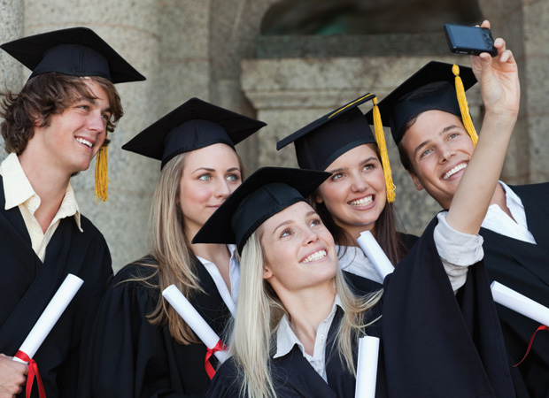 Students in cap and gowns posing for a picture