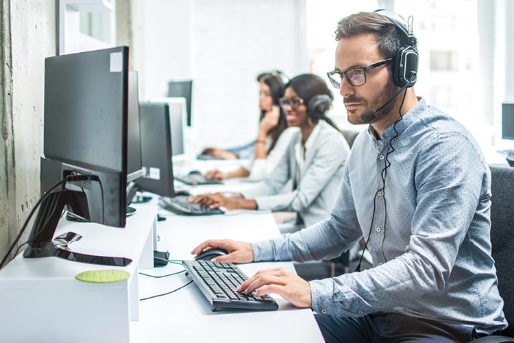 Man wearing phone headset on computer