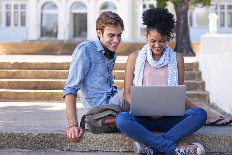Boy and girl sitting on sidewalk looking at laptop