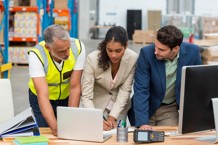 Three logistics professionals collaborating over computer in warehouse