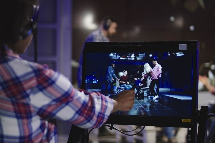 Film producer in headset controlling process of shooting TV in front of computer screen