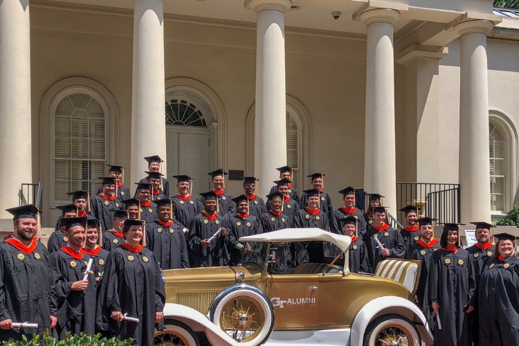 Graduates in caps in gowns standing next to the Ramblin' Wreck