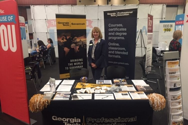 Theresa Atkins standing being the Georgia Tech booth