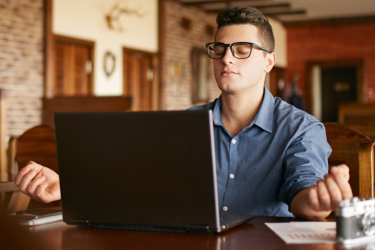 Adult professional taking a meditation break in front of laptop