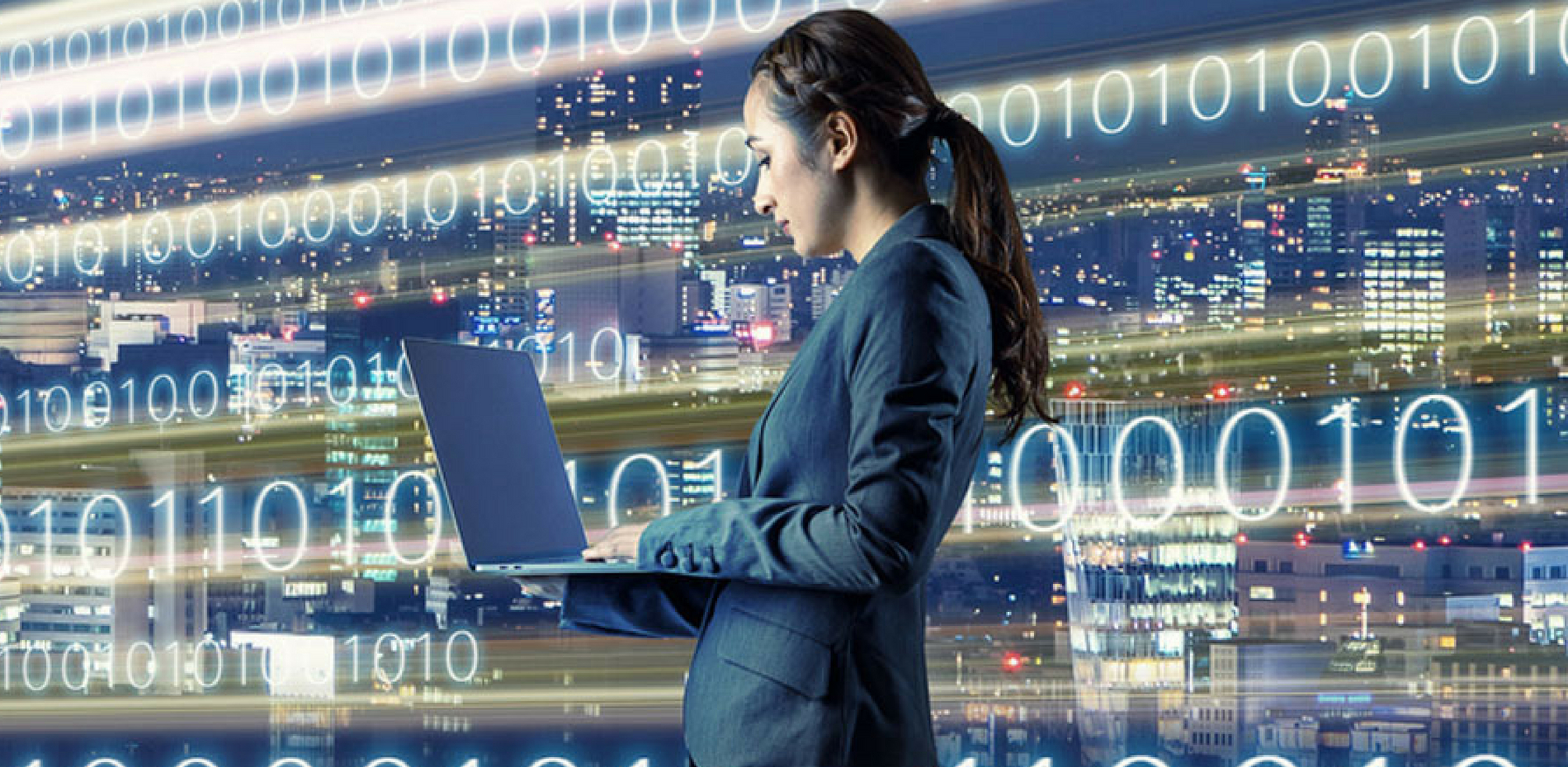Woman standing in front of backdrop of code holding a laptop