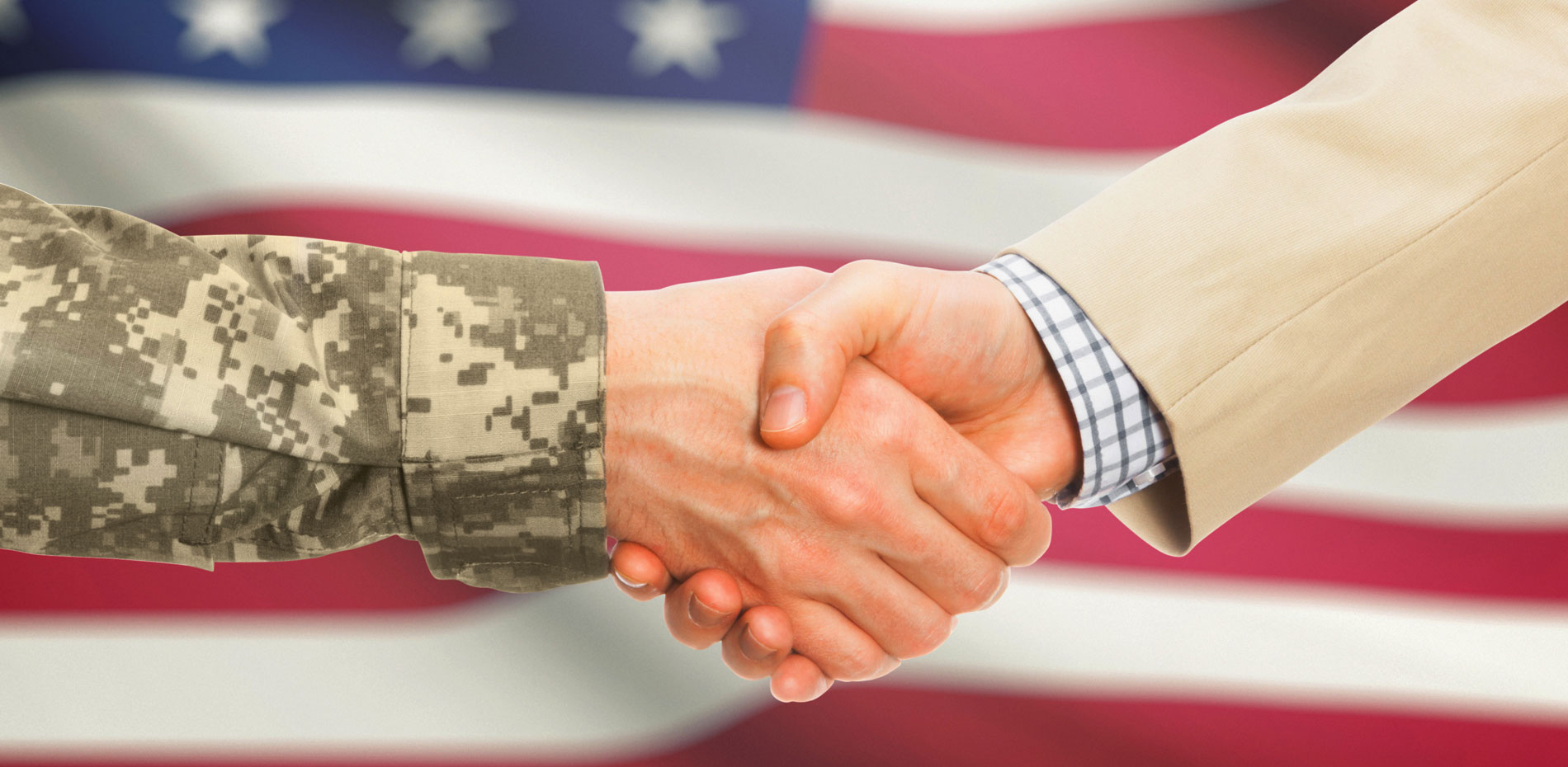 Two hands shaking, one in suit and one in military uniform with the american flag as a backdrop