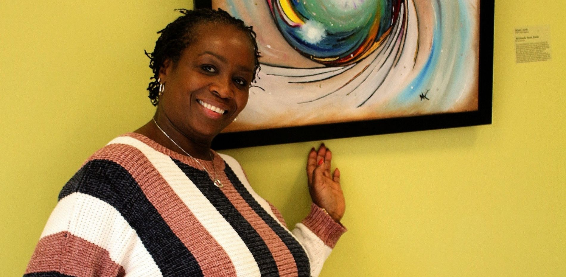 """Mimi Lewis, academic programs coordinator, stands next to her featured artwork entitled """"All Roads Lead Home."""""""