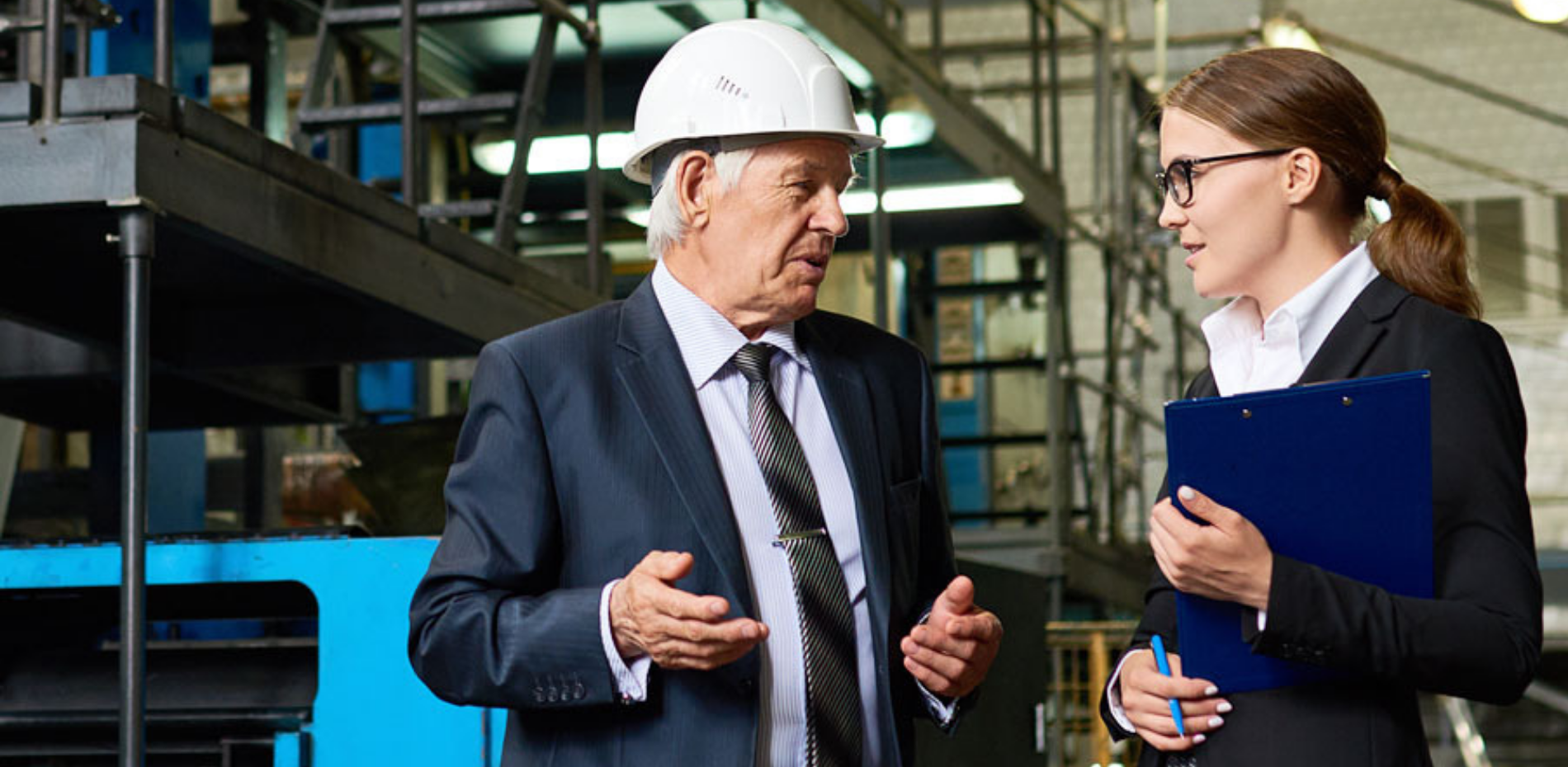 Man wearing hard hat talking to woman in front of factory equipment
