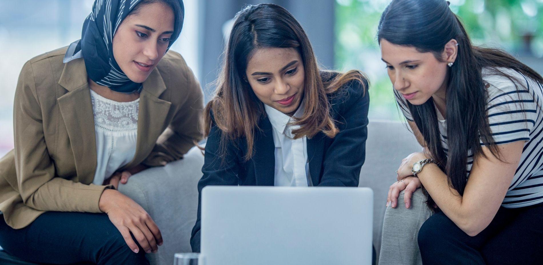Three women in financial technology sector collaborating over computer screen