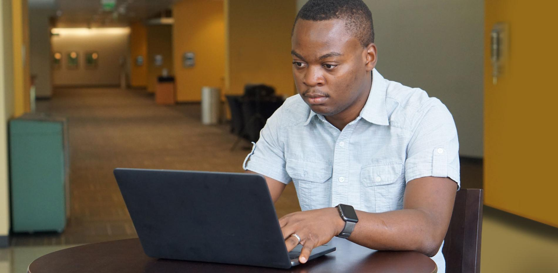 Esterling Accime working in front of laptop