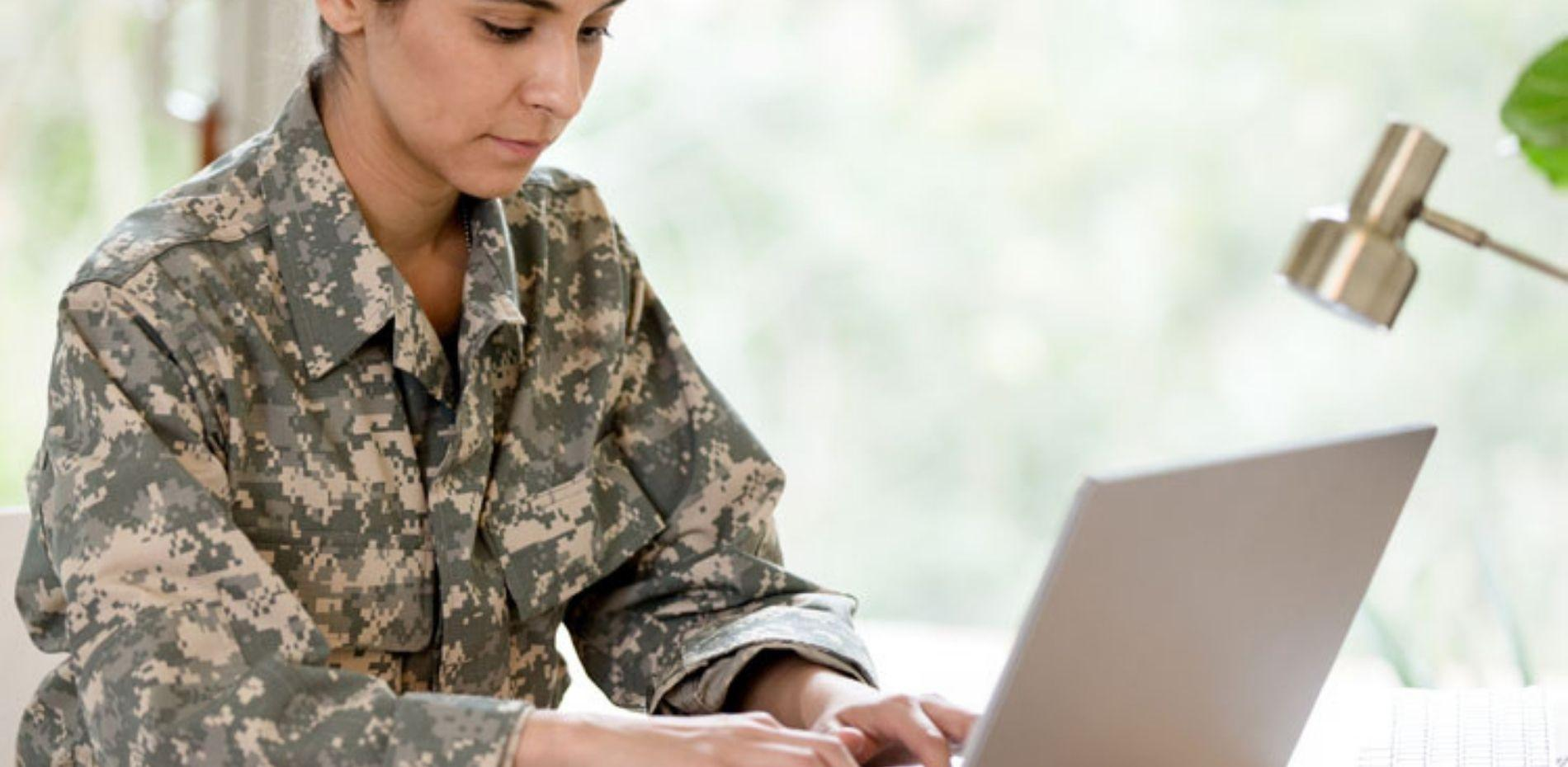 Female solider learning on laptop