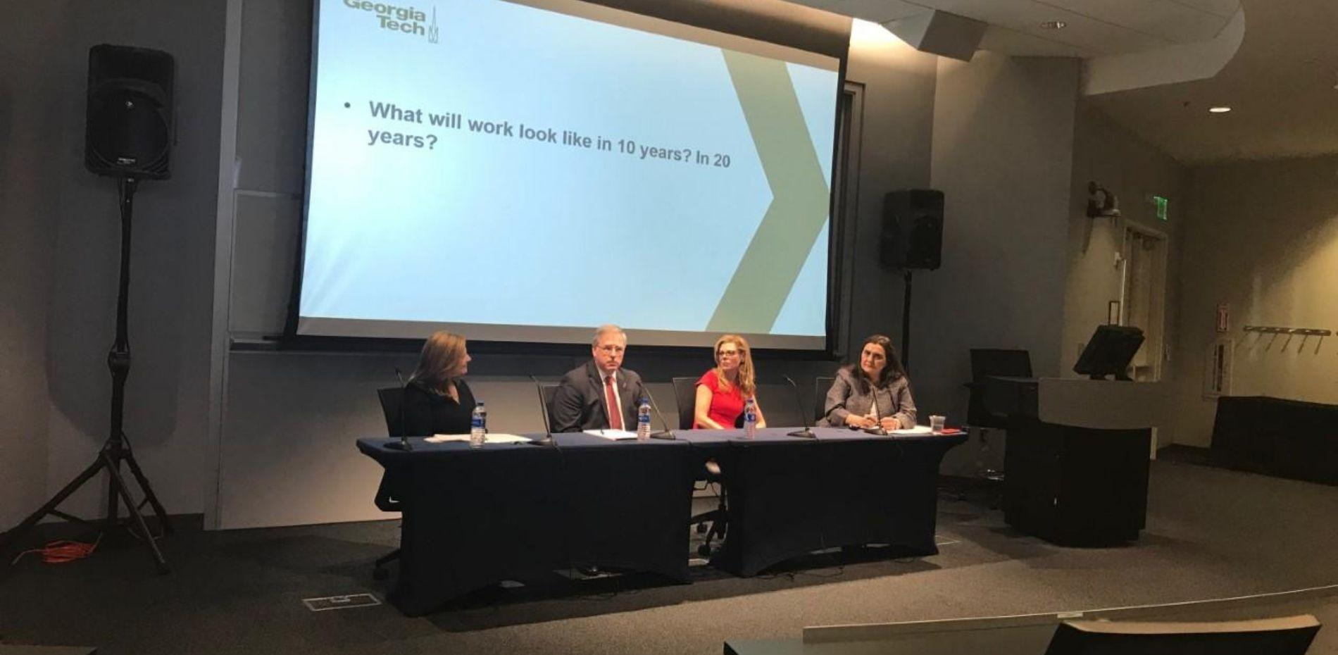 """The panelists sit at the front of the room with the question """"what will work look like in 10 years?"""" behind them"""