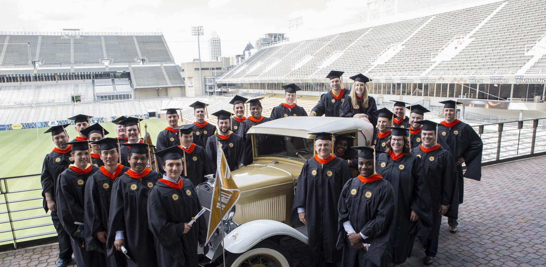 Professional Master's in Applied Systems Engineering graduates stand need to Ramblin Wreck at Bobby Dodd Stadium
