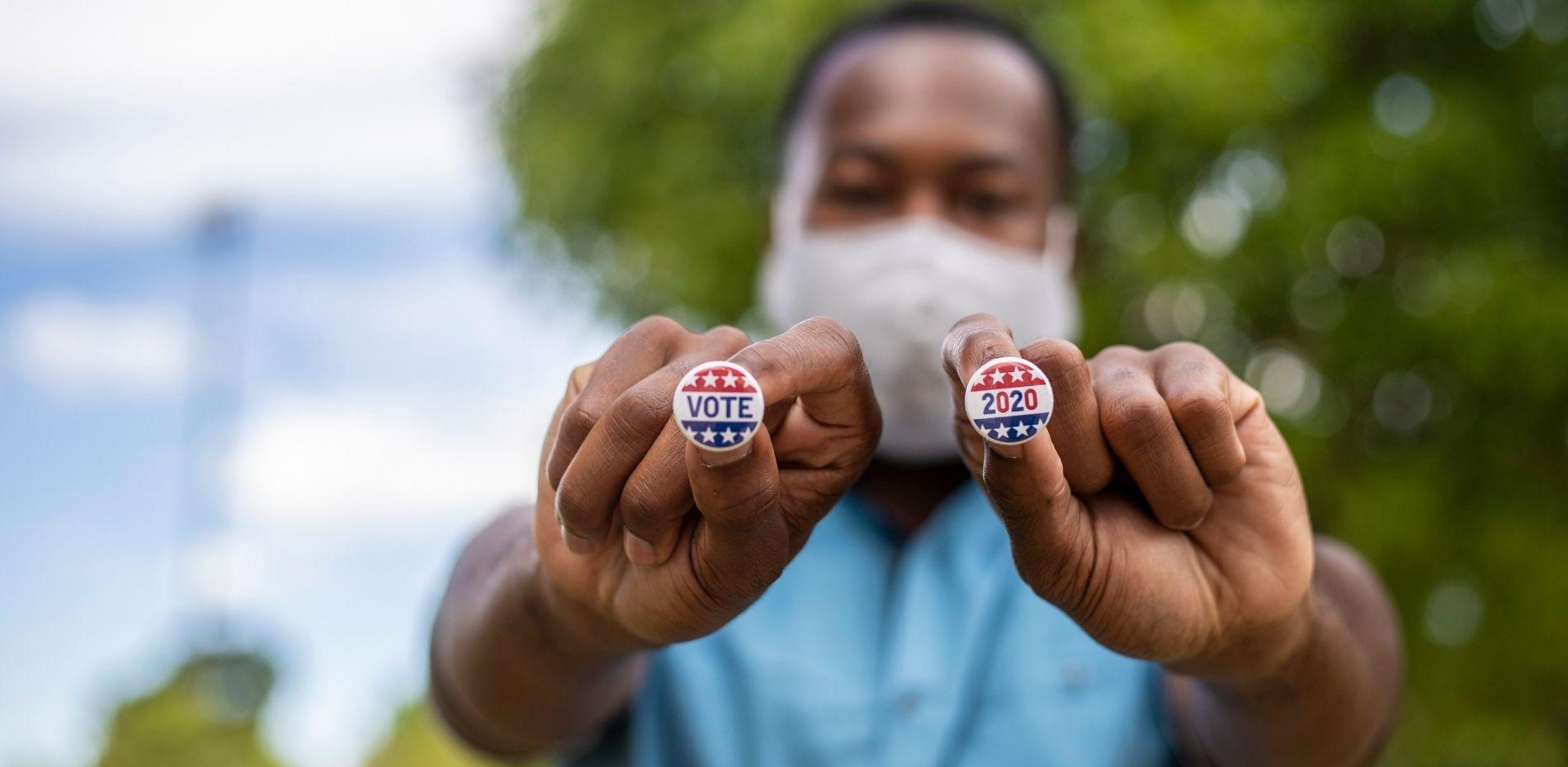 Male voter holding voting pins right after voting.