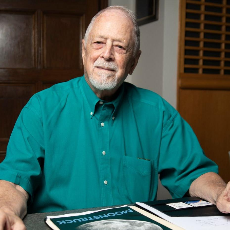 Bob Macdonald, online masters in analytics student, sits at table with historic moon landing documents in front of him.