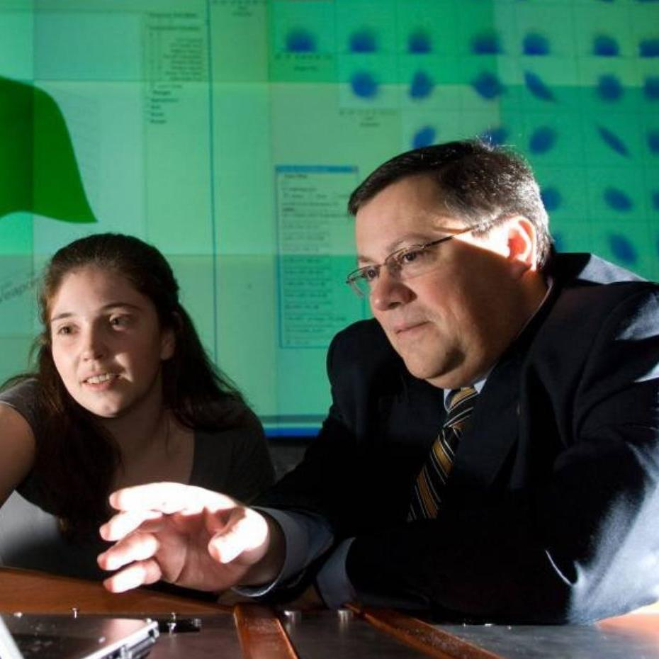 Dimitri Marvis and a female student sitting at a desk in a classroom, looking at a laptop screen.