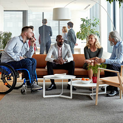 A group of diverse coworkers sit around couches in office to meet
