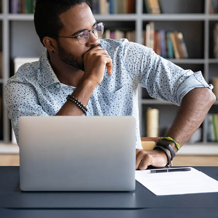 Male professional working on laptop while looking to the side in thought