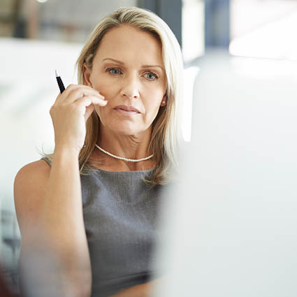 Female professional with uncertain face stares at laptop