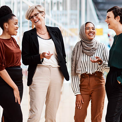 Group of female coworkers smiling and laughing outside office building