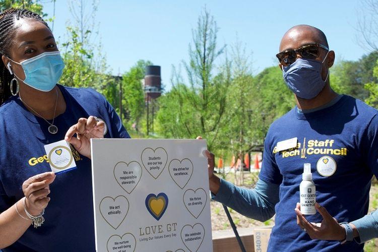 Georgia Tech employees handing out L.O.V.E. GT stickers