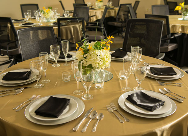 Round banquet table with tablecloth and place settings for an event