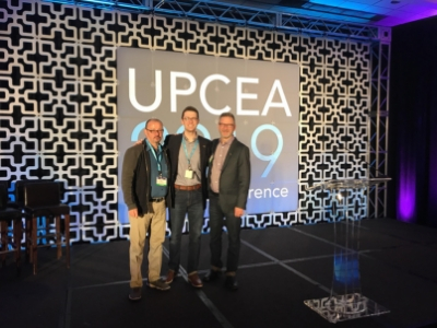 Mont Rogers, Stephen Fain, and Chris Walker posing on stage at the 2019 UPCEA Annual Conference