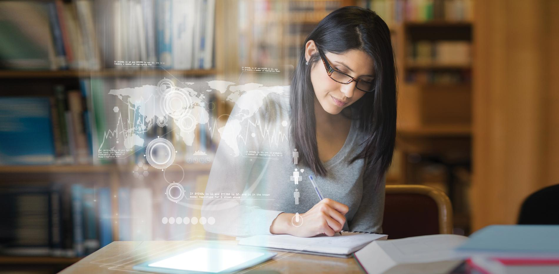 Woman looking over book with digital images in front of her