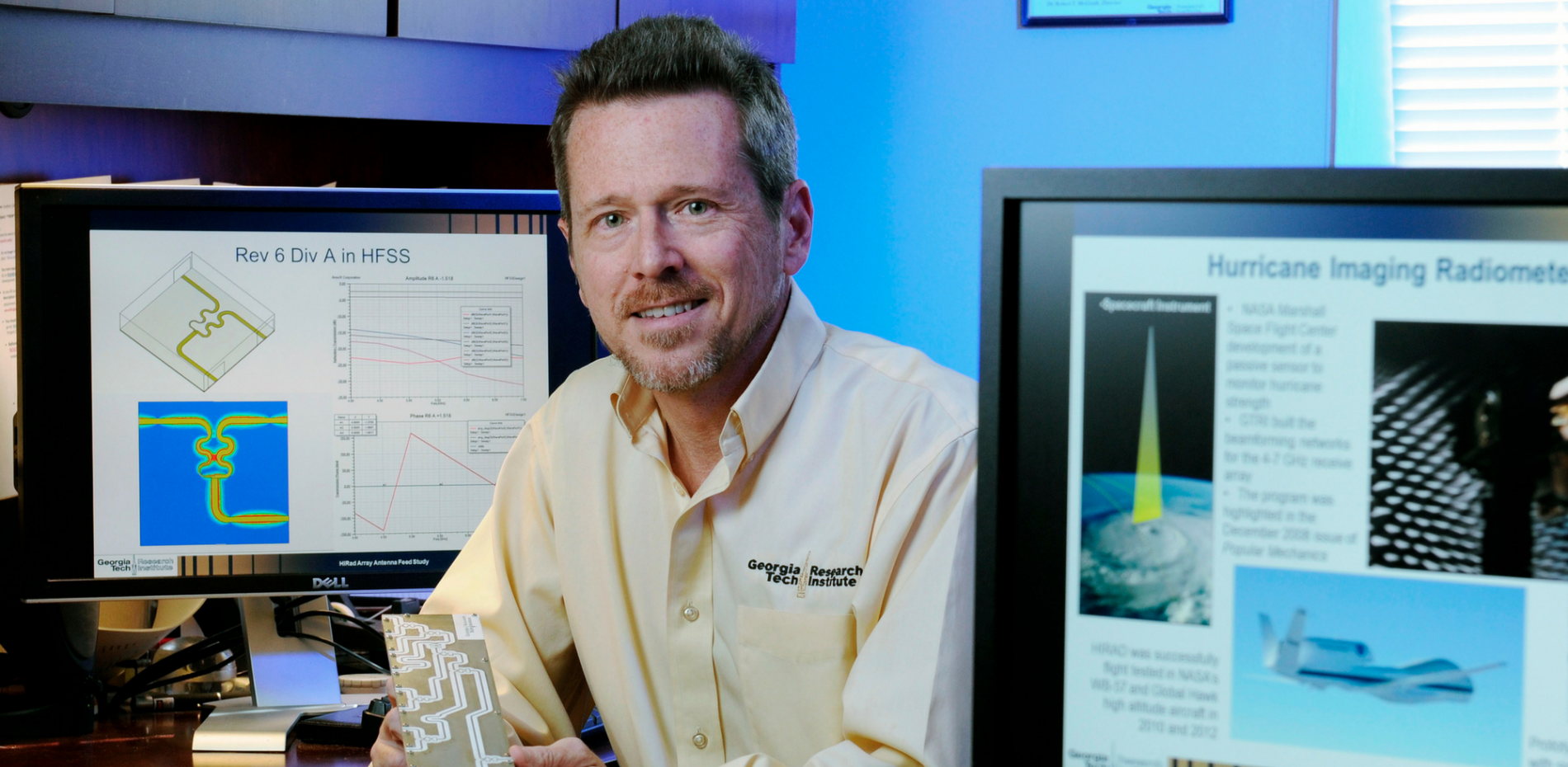 Glenn Hopkins next to computer screens displaying research
