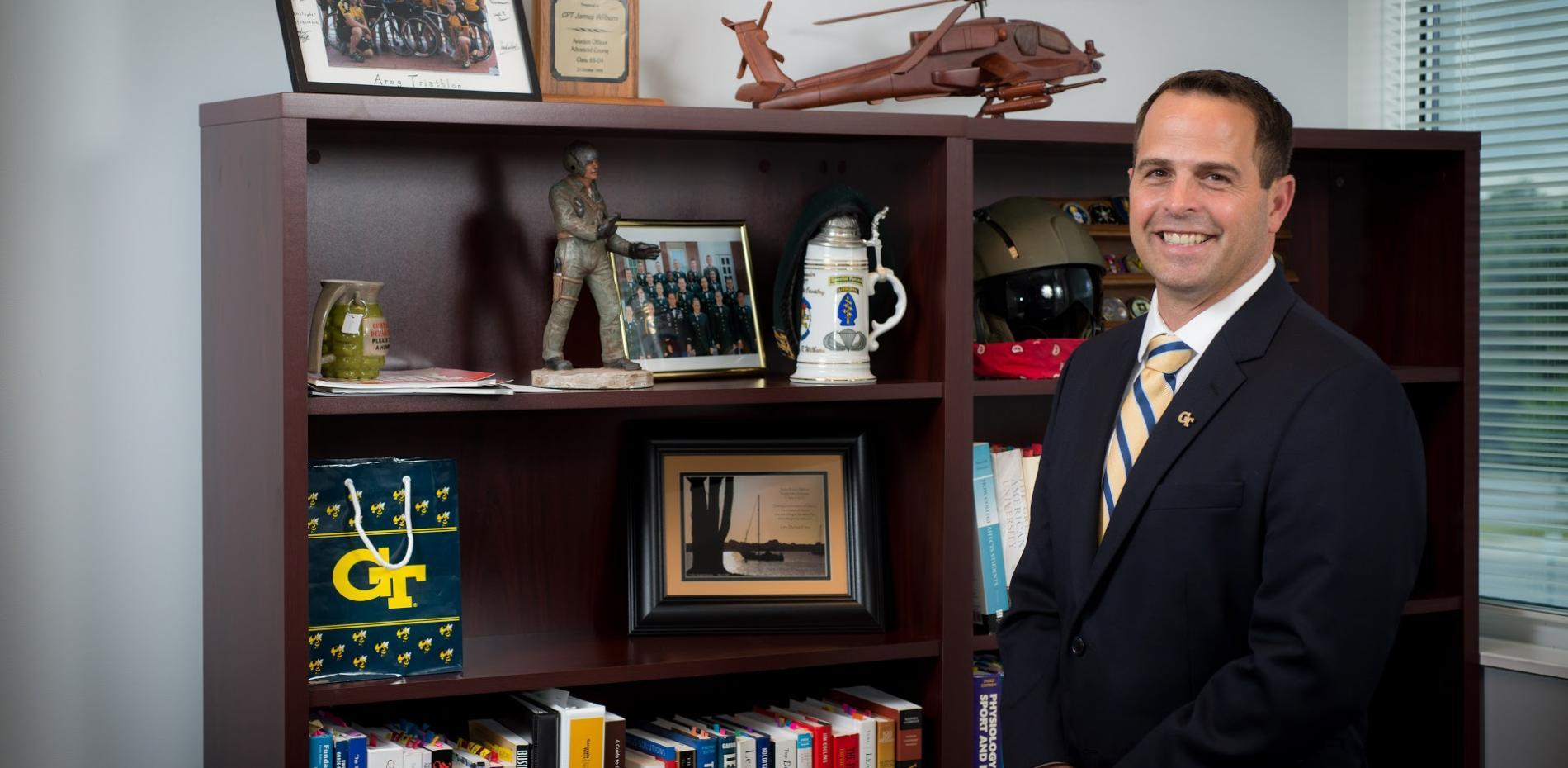 James Wilburn standing in front of bookshelf in his office with military memorabilia