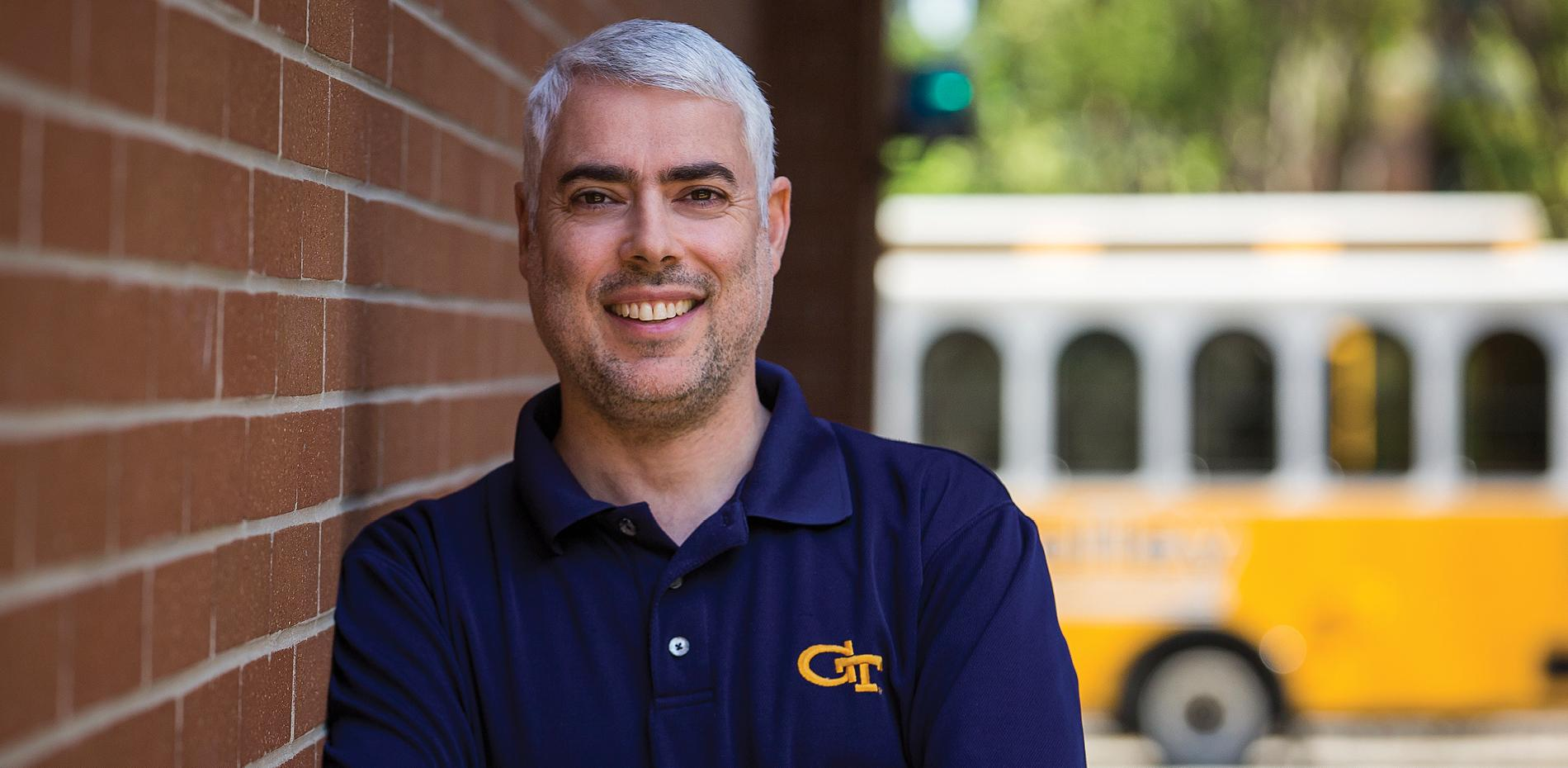Joel Sokol smiles while he leans against a brick wall. The Georgia Tech Trolley passes in background.