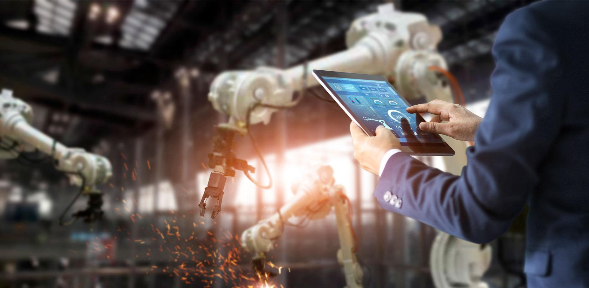 A person wearing a blue suit (only hands and forearms are visible) is controlling robots via a tablet.