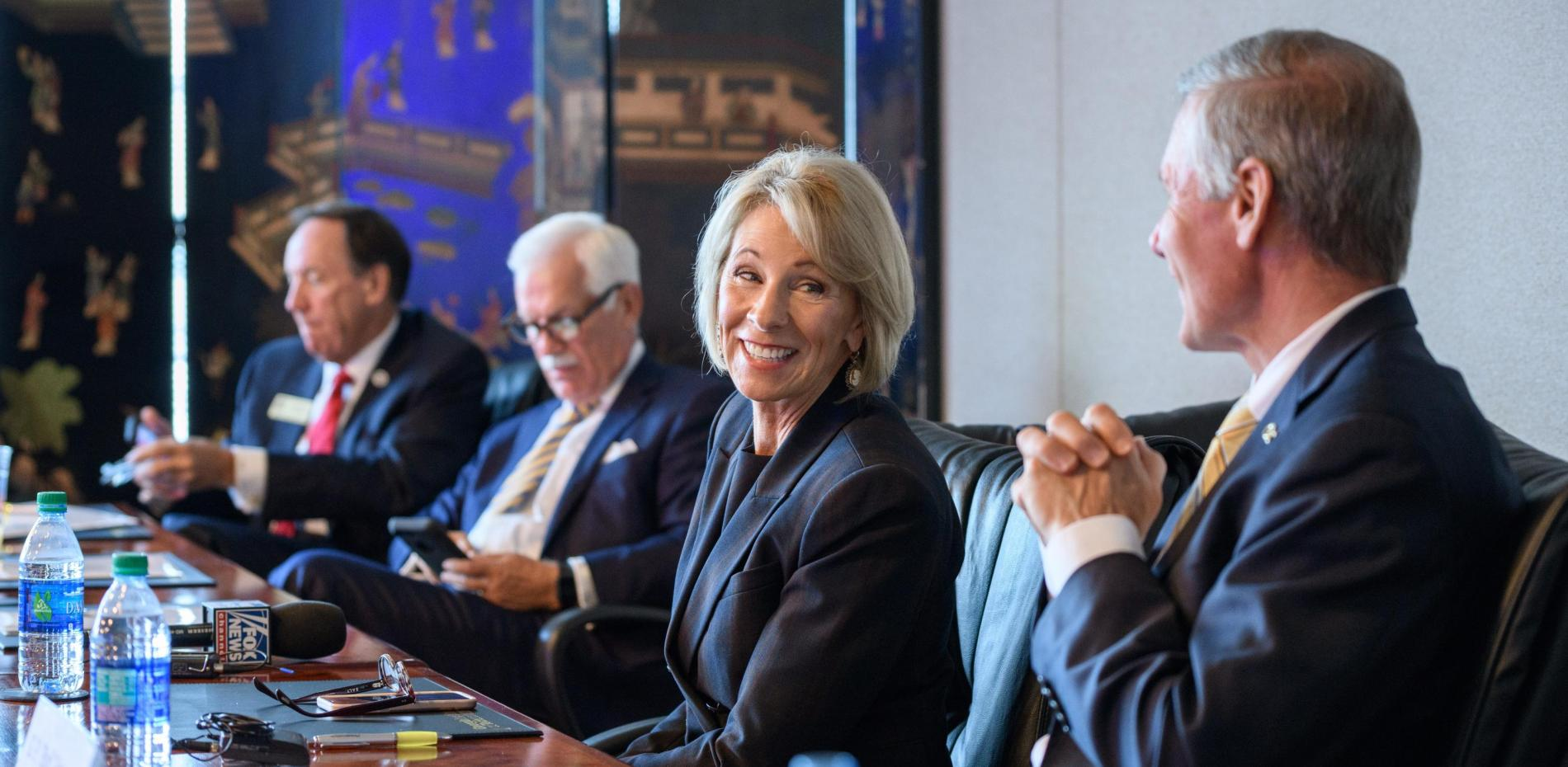 Betsy DeVos sitting at conference table with members of Georgia Tech leadership