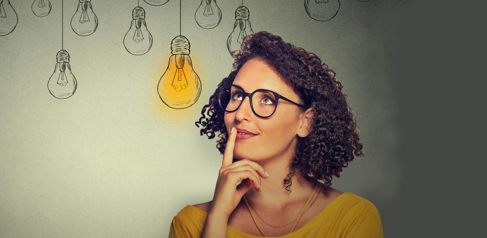 Woman looking inspired with light bulbs in background