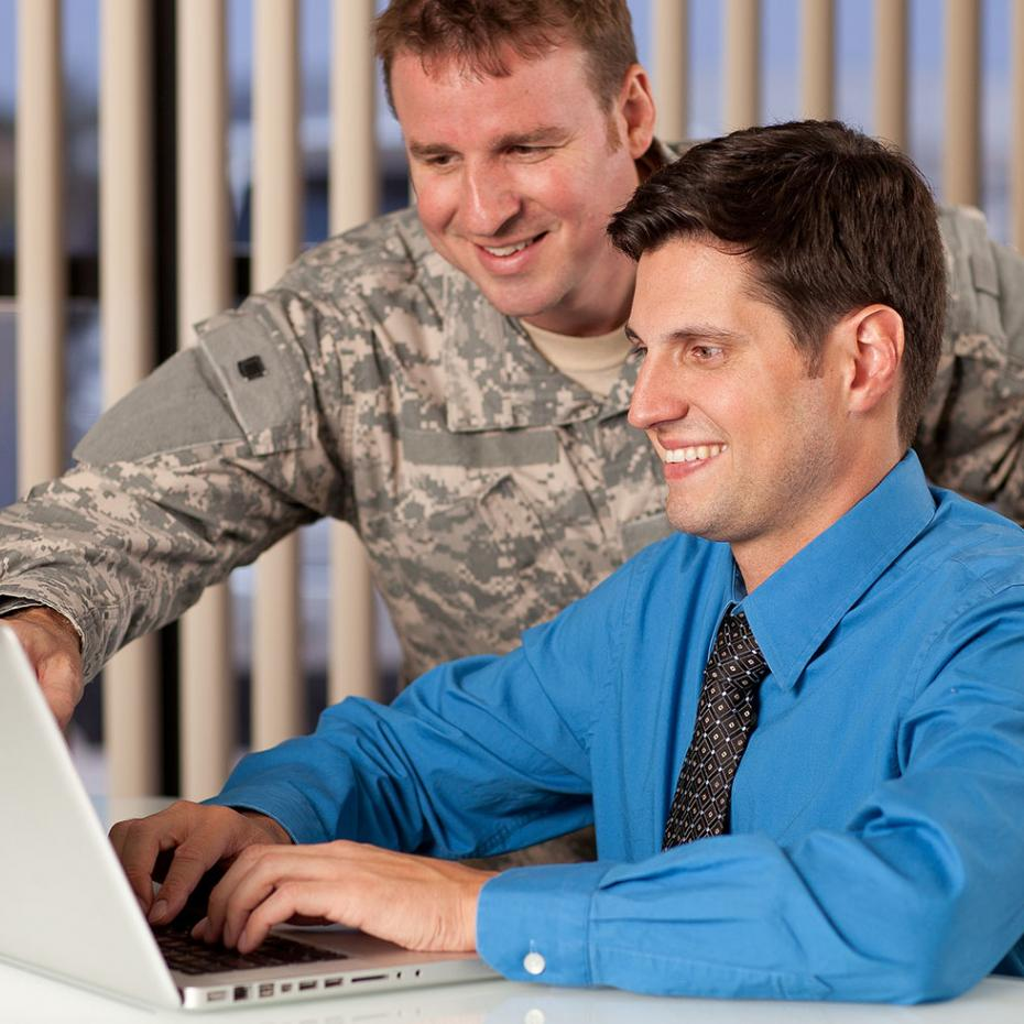 Military personel assisting working professional at computer