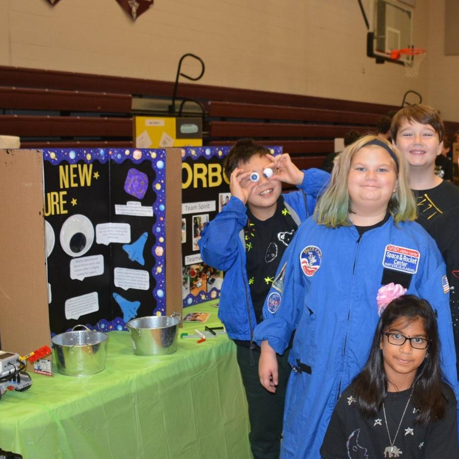 Lego League team poses for picture next to their project board and wearing space gear